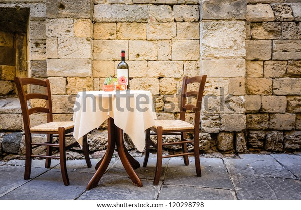 table and chairs in front of historic wall - tuscany/italy