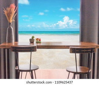 Table and chairs in front of the window with sea view.