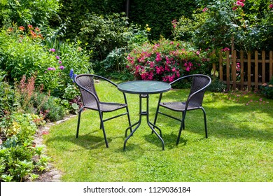 Table and chairs in the garden full of summer flowers