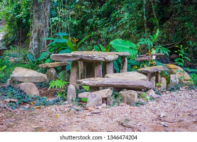Table and chairs made of stone in a tropical forest, a rest spot