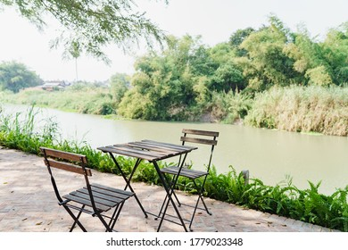 Table and chairs near the river and green forest view.