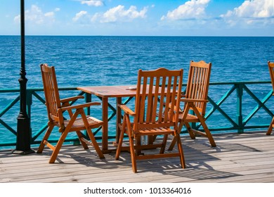 Table and chairs on balcony of restaurant near the sea