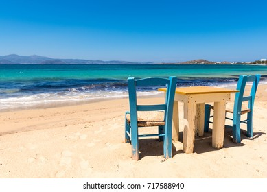 Table with chairs on the beach with beautiful sea view. Agia Anna village on Naxos Island. Greece.