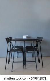 table with chairs on the floor and gray background.