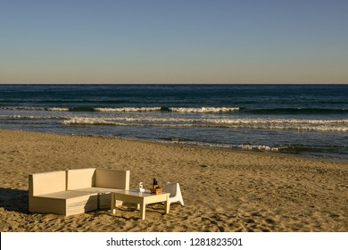 Table and chairs on a sandy beach by the shore with waves at sunset, Alassio, Liguria, Italy