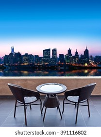 Table and chairs on a terrace, view on a city (Shanghai) at night