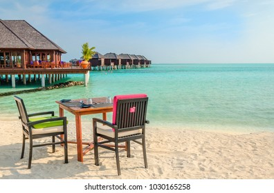 Table and chairs at restaurant at the background of water bungalows, Maldives