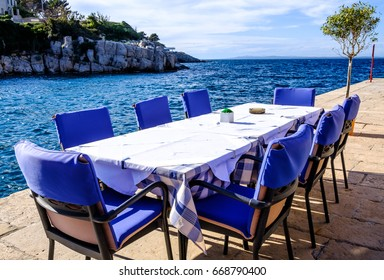 table and chairs at a sidewalk restaurant at a harbor in croatia