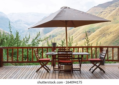Table and chairs under umbrella on terrace against awesome mountains. Shot in Tsehlanyane Nature Reserve, Lesotho.