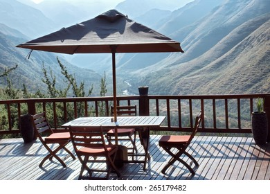 Table and chairs under umbrella on terrace against blue mountains. Shot in Tsehlanyane Nature Reserve, Lesotho.
