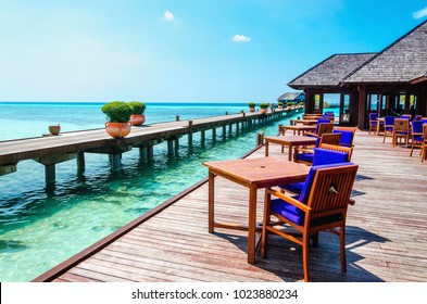 Table and chairs at water restaurant at the background of the blue sky in tropical Maldives island