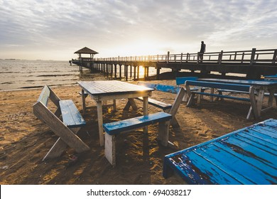 table chairs with wood bridge in sea,sunset on the beach