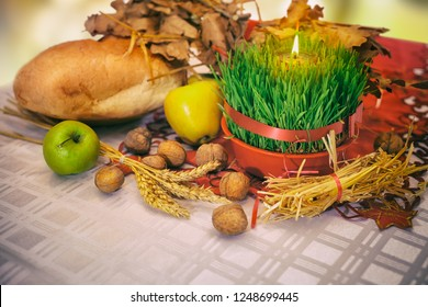 Table with Christmas decoration. Christmas offerings with Christmas wheat, bread, apples and walnuts