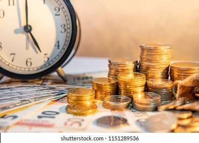 Table clock and gold coin stack on the table with international banknotes currency. Time investment and passing time. Urgency countdown timer for business deadline concept