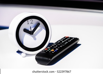 Table clock and remote control on desk