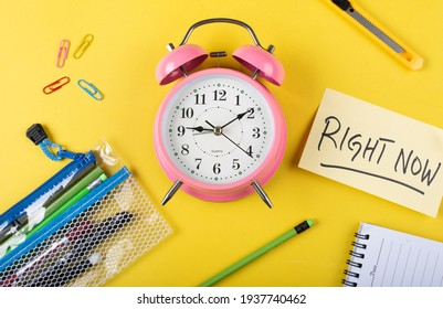 A table clock with Right now words Written on a sticky note with other elements on a Yellow background flat lay shot