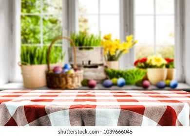 Table clothe of red and white color with blurred window and easter decoration.