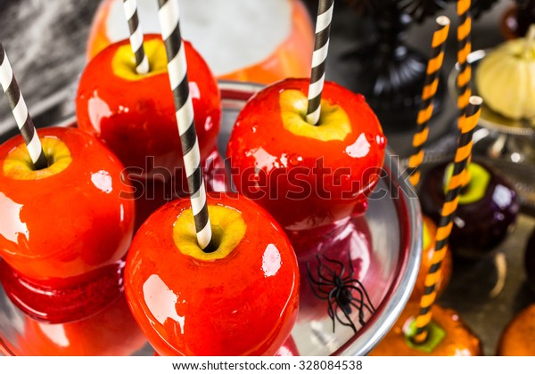 Table with colored candy apples for Halloween party.