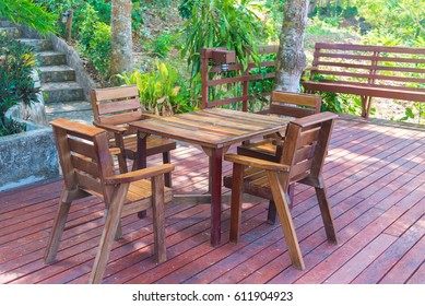 Table corner on wooden terrace, vintage solid wood furniture with mountain and river at resort.