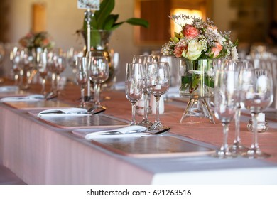 Table covered with tablecloth at wedding reception, decorated with flowers in vases. Selective focus on glasses