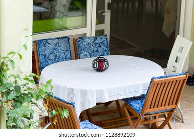 table covered with white tablecloth and chairs near house