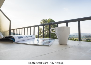 Table with cup of coffee and magazine  on a terrace with a beautiful view