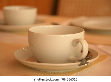 Table with cup, plates and spoon.