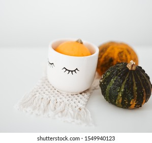 Table cup are there with pumpkin. Cup is looking great in this picture. Cup and pumpkin is there on the table.