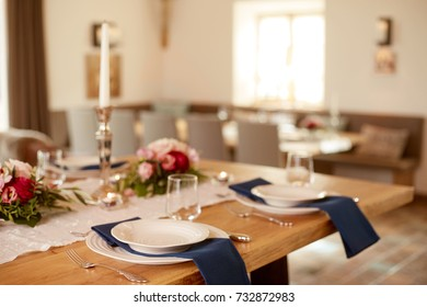Table decor with white plates on blue napkins and small flowers in big open space