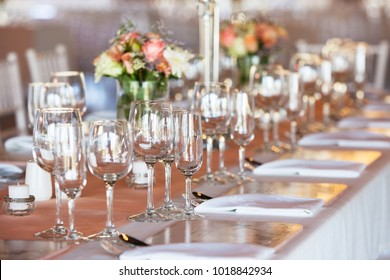 Table decorated with flowers, crockery and cutlery at wedding reception
