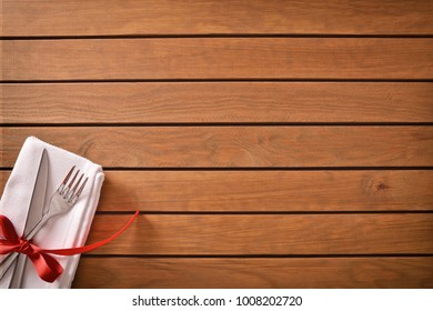 Table decorated with red tie for special event and planked wood table background. Top view
