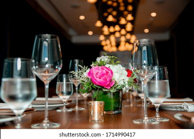 table decorated with white plate and roses. Flowers on a table in a vase. White and pink roses.