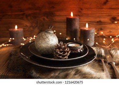 Table decoration with candle lights and christmas accessoires in country house style for a festive dinner