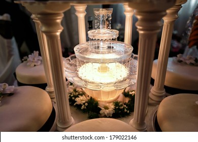 Table decoration of champagne fountain in light and wedding cakes around