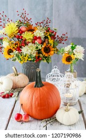 Table decoration with pumpkins, sunflowers and dahlias. Candles inside vintage bird cages and paradise apples. Postcard motif.