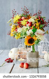 Table decoration with sunflowers and dahlias. Candles inside vintage bird cages, pumpkins and paradise apples. Postcard motif.