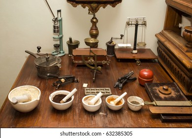 A table with different ancient instruments, scales and mortars for making medicines