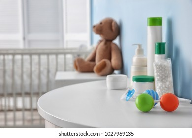 Table with different baby accessories in children room