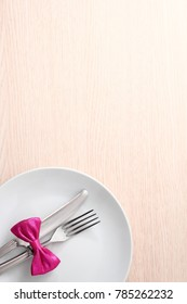 Table with dish, cutlery and pink bow.