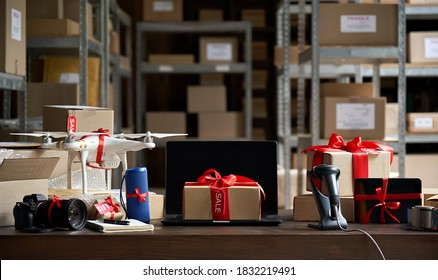 Table with electronic devices, laptop and gift box on table, warehouse storage background. Ecommerce gadgets store website discounts and gifts. Black friday and cyber monday best buy offers concept.