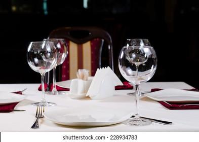 Table in Fancy Restaurant Set for Dinner with Wine Glasses