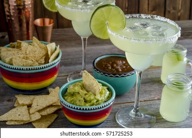 Table filled with glasses filled with classic lime margarita cocktails, tortilla chips, salsa and guacamole