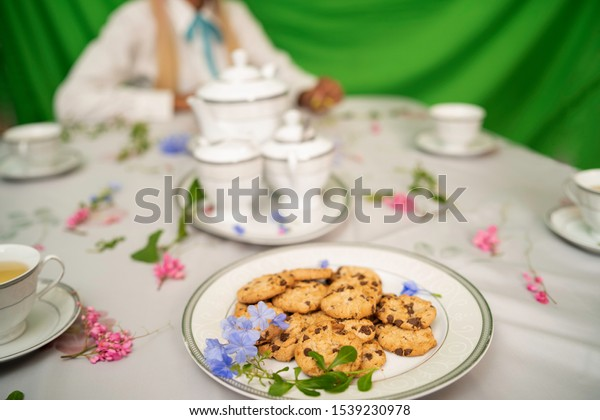 Table with a floral cover and a plate of chocolate biscuits or oatmeal cookies and a set of tea with green background.