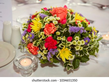 Table flower arrangement with lit candles, set up for an event or wedding.