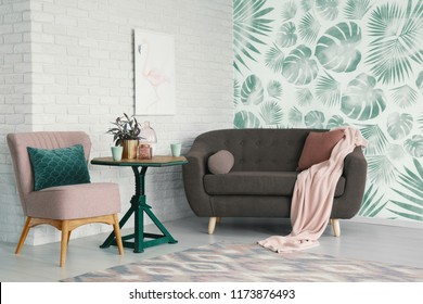 Table with flowers between pink chair and settee in apartment interior with poster and wallpaper. Real photo
