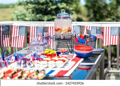 Table with food and drinks set for celebrating July 4th on the back patio.