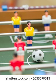 table football detail of colorful players (figurines), one of them and ball in focus the others out of focus