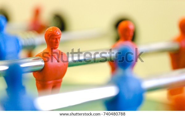 Table football, foosbal red and blue players in macro view. Low angle detailed view with selective focus and shallow depth of field.