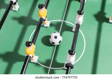 Table football game with white and yellow players team in table soccer or football kicker game