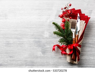 Table fork and knife set with napkin, christmas fir branch, red berries and ribbon on gray wooden background copy space